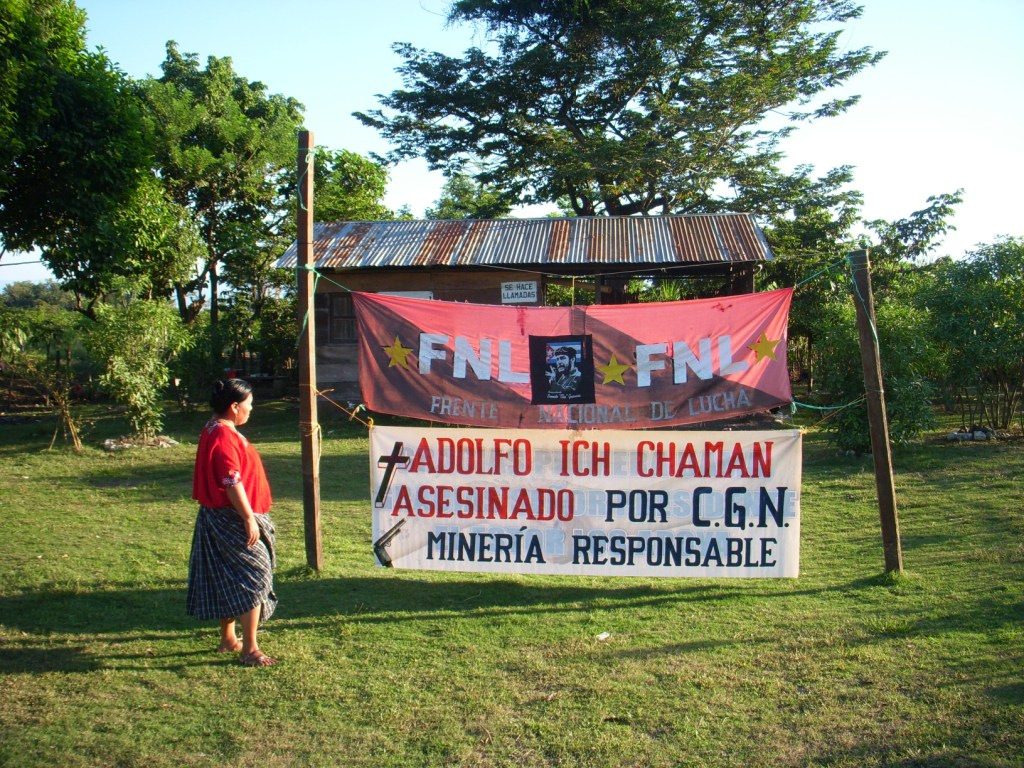 "Angelica Choc stands next to a sign that says ""Adolfo Ich murdered by CGN. Mining is responsible.""  Photograph by Daniel Sosa"